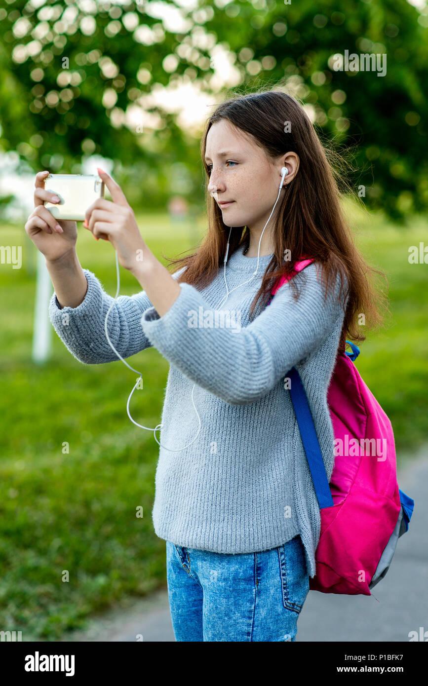 Una ragazza adolescente. In estate la natura. Brunette con lentiggini sul  suo viso. Fa una foto su strada. Dietro la schiena è una rosa nello zaino. 838c0873ec04