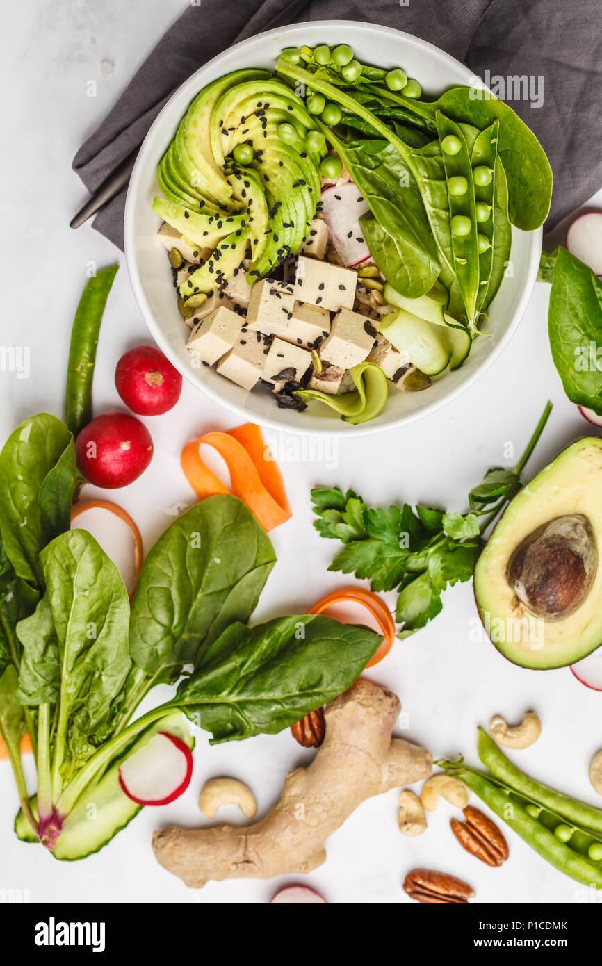 Cibo sano laici piana. Ciotola di Buddha con tofu, riso, avocado e verdure. Sano cibo vegan concetto. Immagini Stock