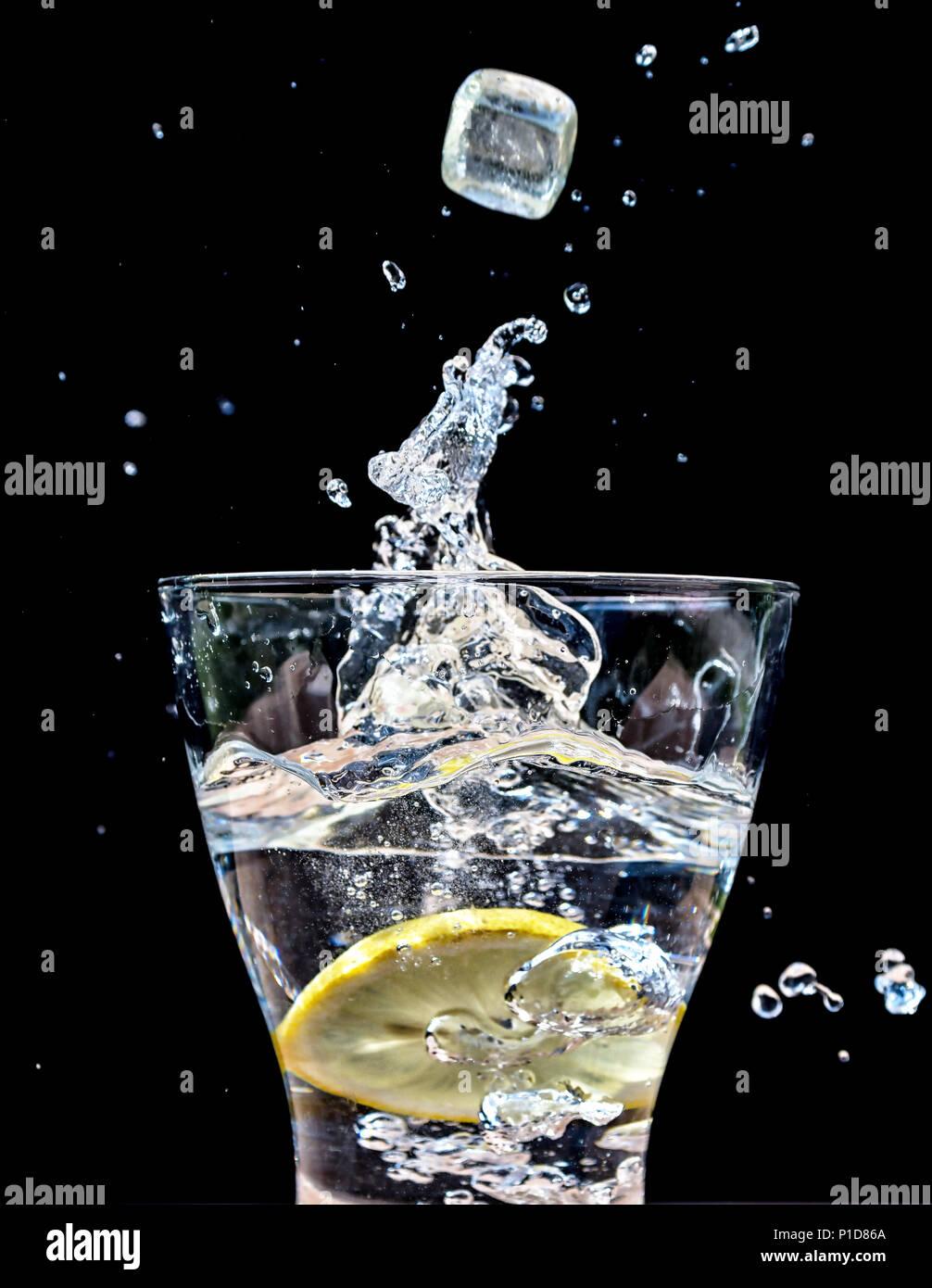 Cubetti di ghiaccio che cade in un bicchiere di acqua creando una splash Immagini Stock