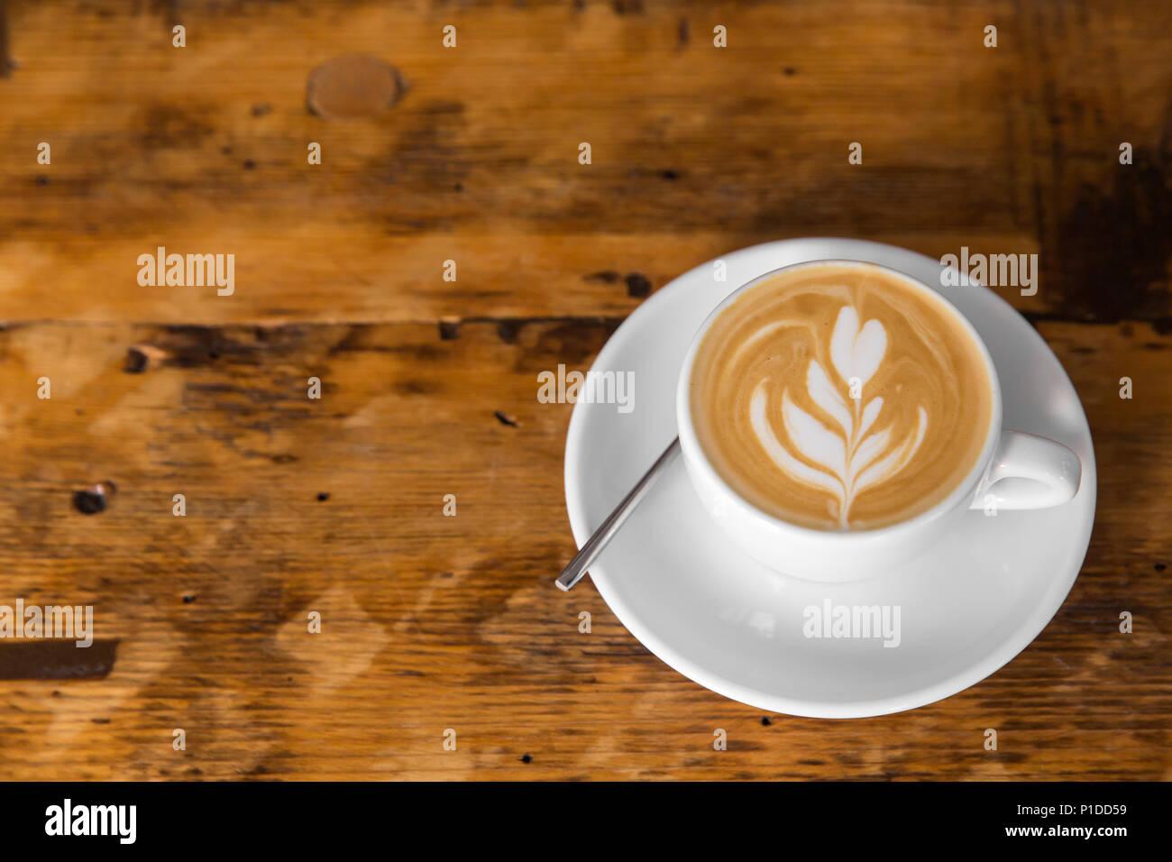 Tazza di caffè per andare sul tavolo di legno con latte art. Street caffè. spazio copia Immagini Stock