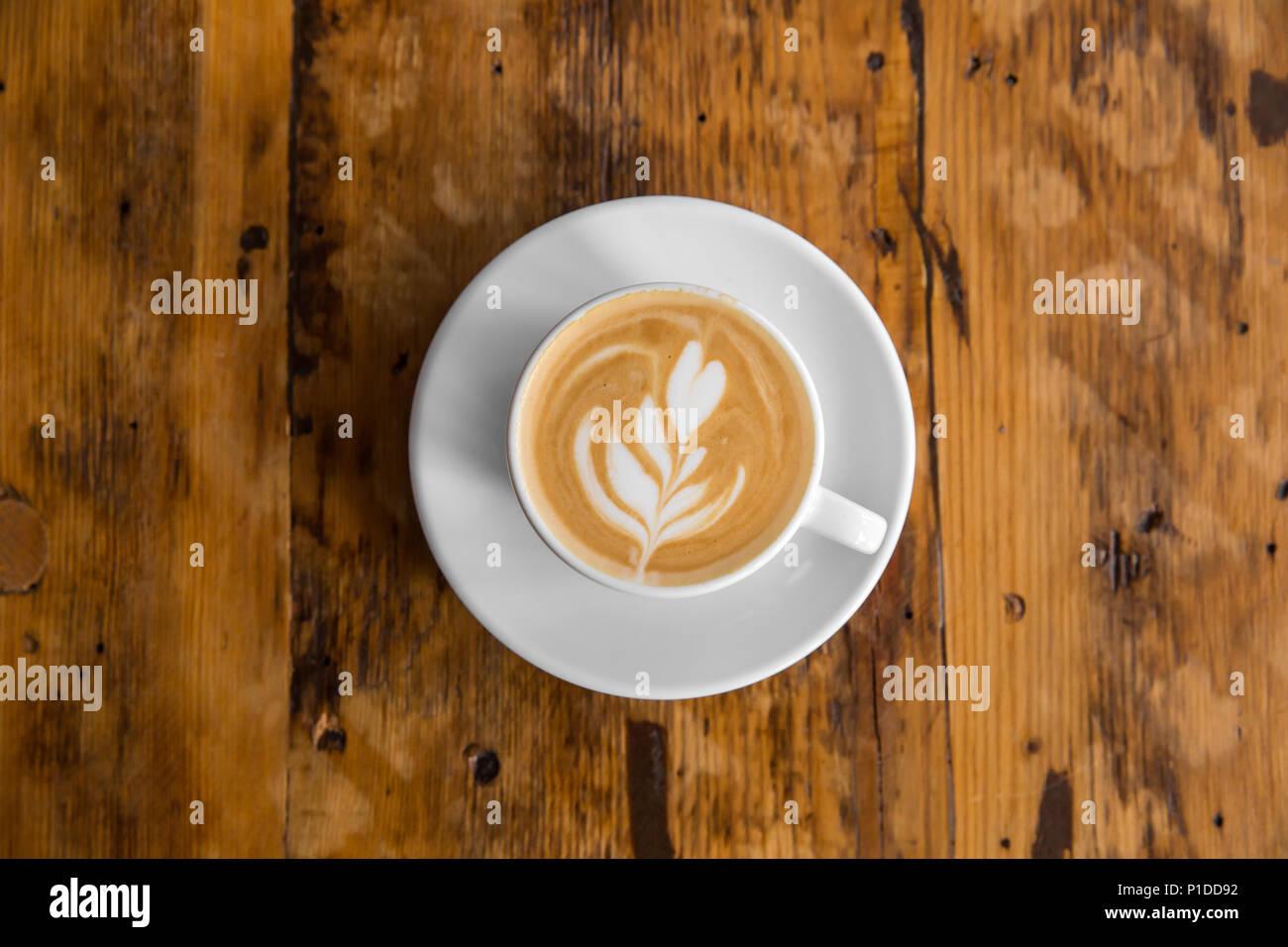 Tazza di caffè per andare sul tavolo di legno con latte art. Street caffè. Vista superiore Immagini Stock