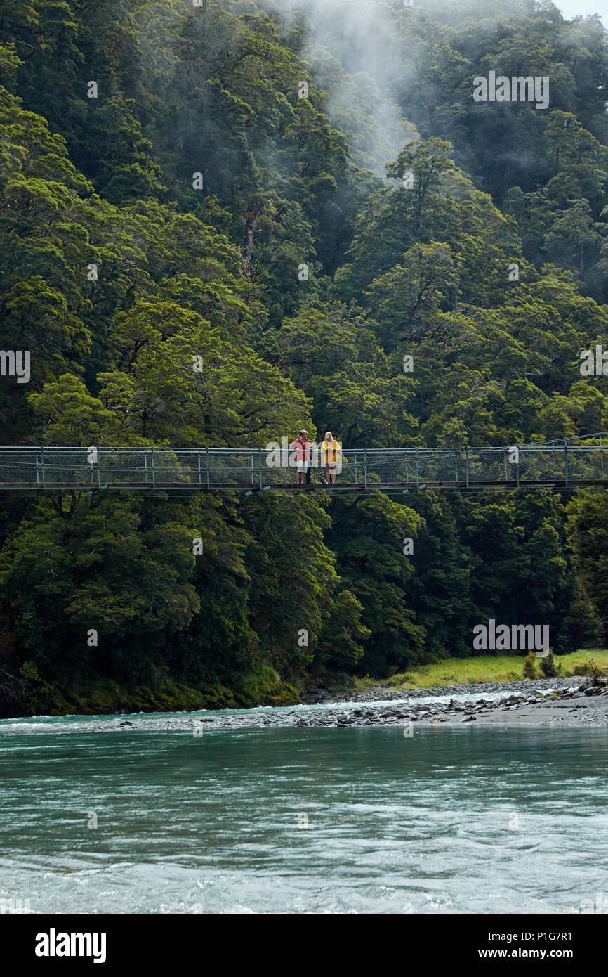 I turisti sulla passerella sul fiume Makarora, Blu Piscine, montare gli aspiranti National Park, Haast Pass, vicino Makarora, Otago, Isola del Sud, Nuova Zelanda (mod Immagini Stock