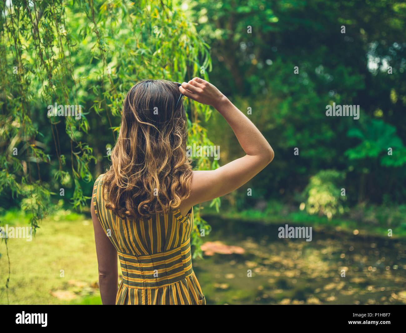 Una moda donna che indossa un abito è in piedi da un laghetto in giardino Immagini Stock