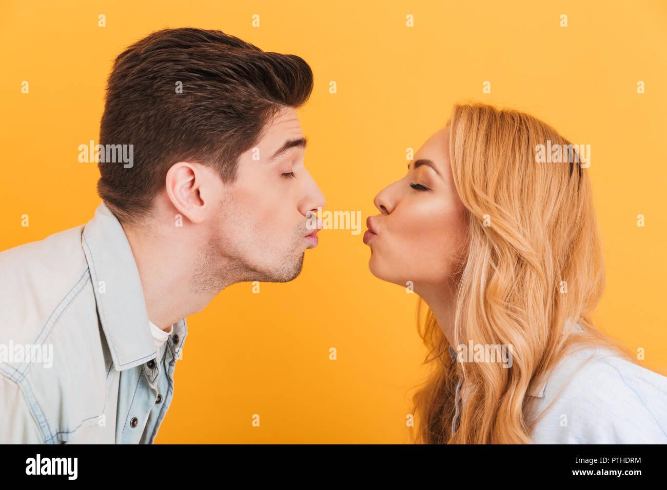 Foto del profilo del giovane bella gente in amore esprimere amore e affetto mentre baciare ogni altro con gli occhi chiusi isolate su backgroun giallo Immagini Stock