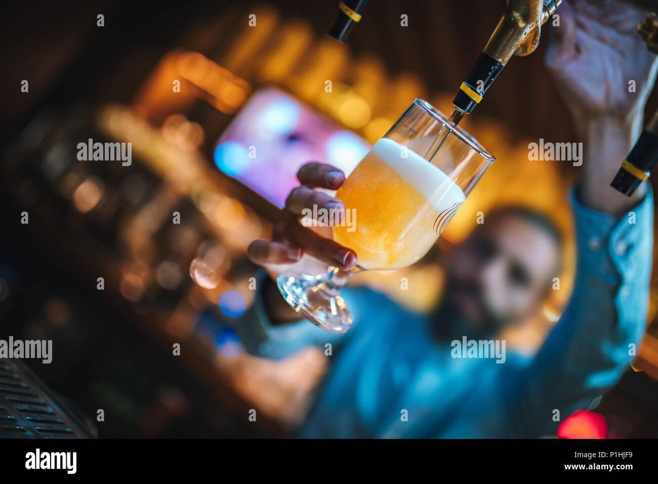 Barman o birraio di riempimento in vetro con la birra. Barman è versando birra chiara a bicchiere da birra rubinetti. Bar o night club interno. Immagini Stock