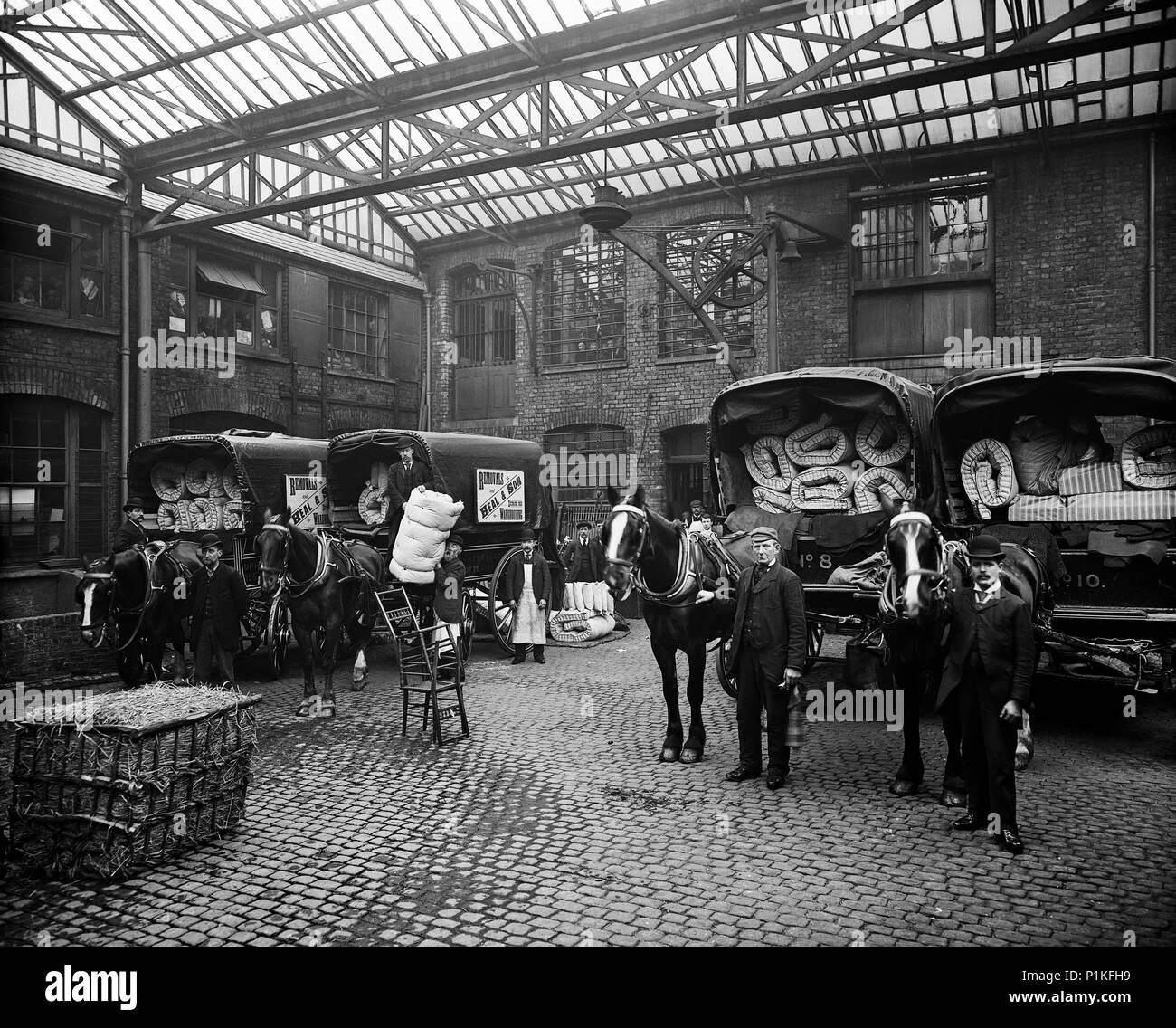 Materasso furgoncini, guarire & Son Ltd, 195-199 Tottenham Court Road, Camden, London, 1897. Personale e carri trainati da cavalli caricati con materassi un Immagini Stock