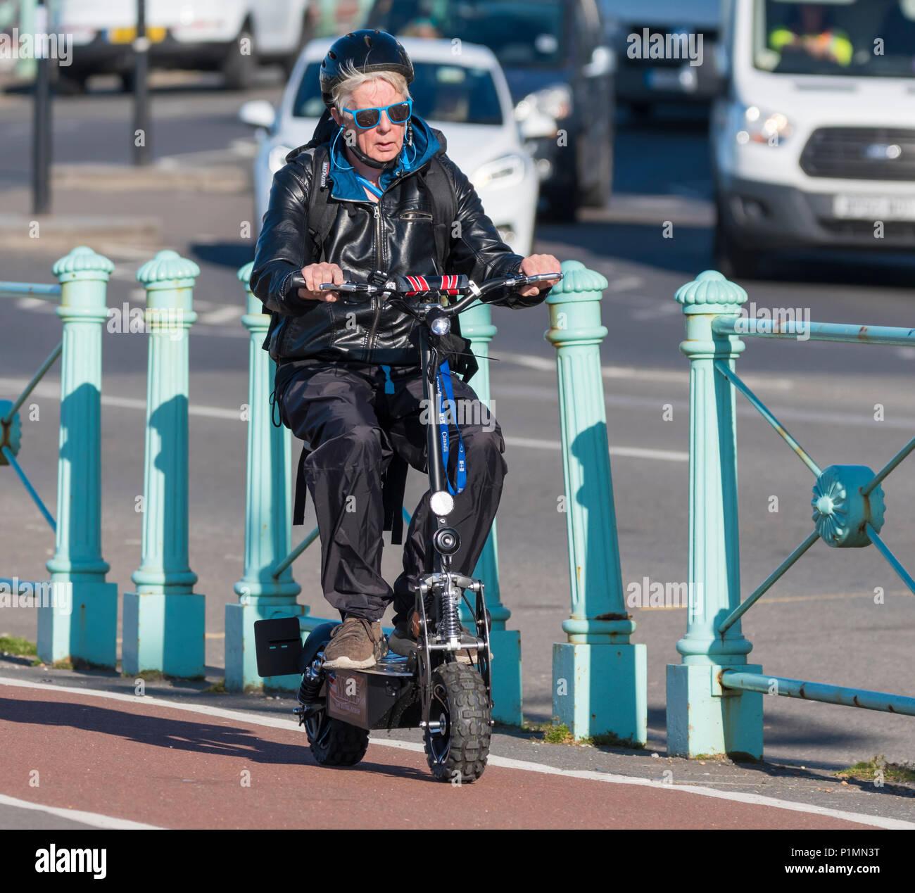 La donna a cavallo di un piccolo scooter elettrico con ruote piccole nel Regno Unito. Immagini Stock
