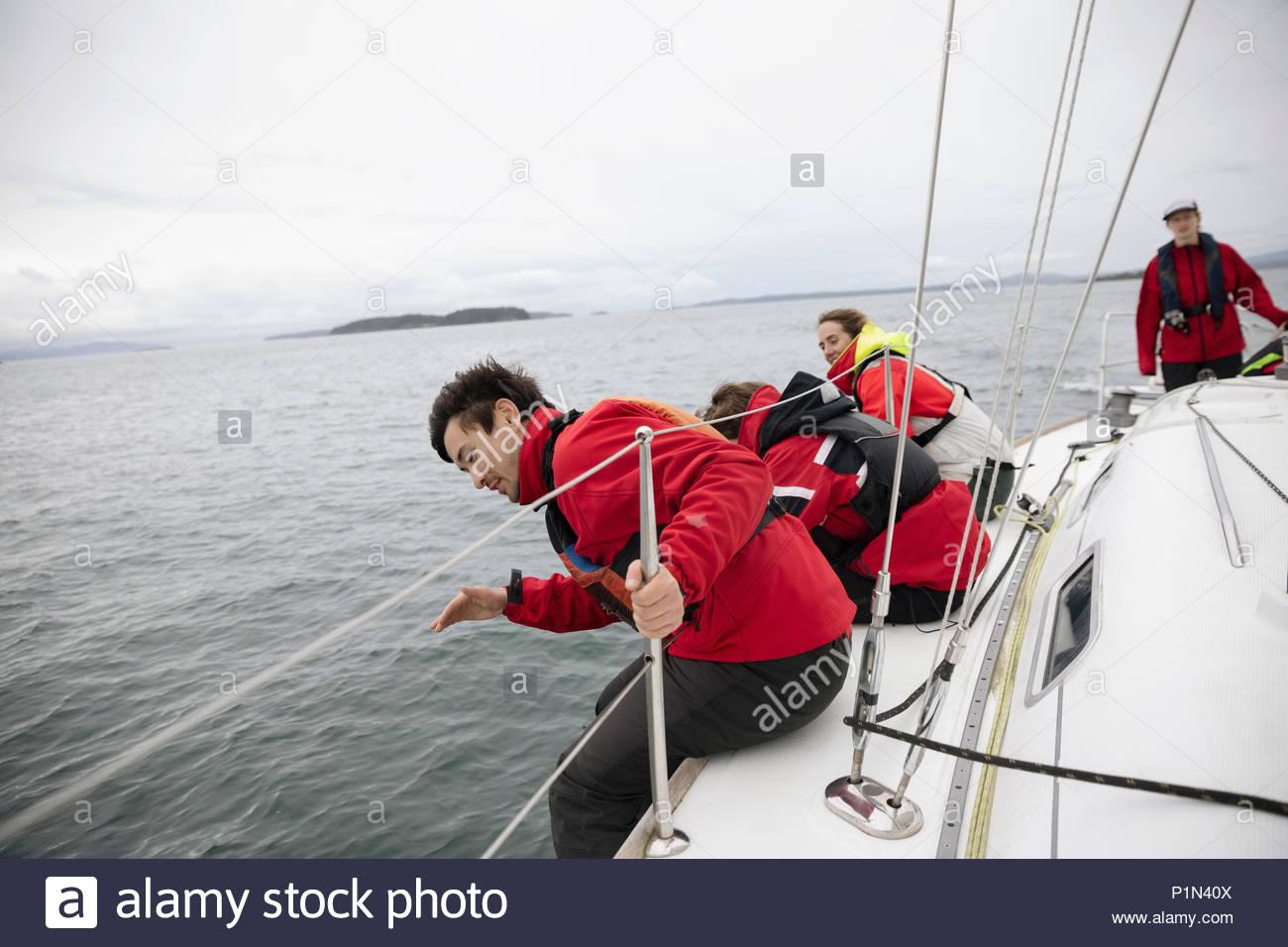 Sailing team seduti a bordo della barca a vela su ocean Immagini Stock