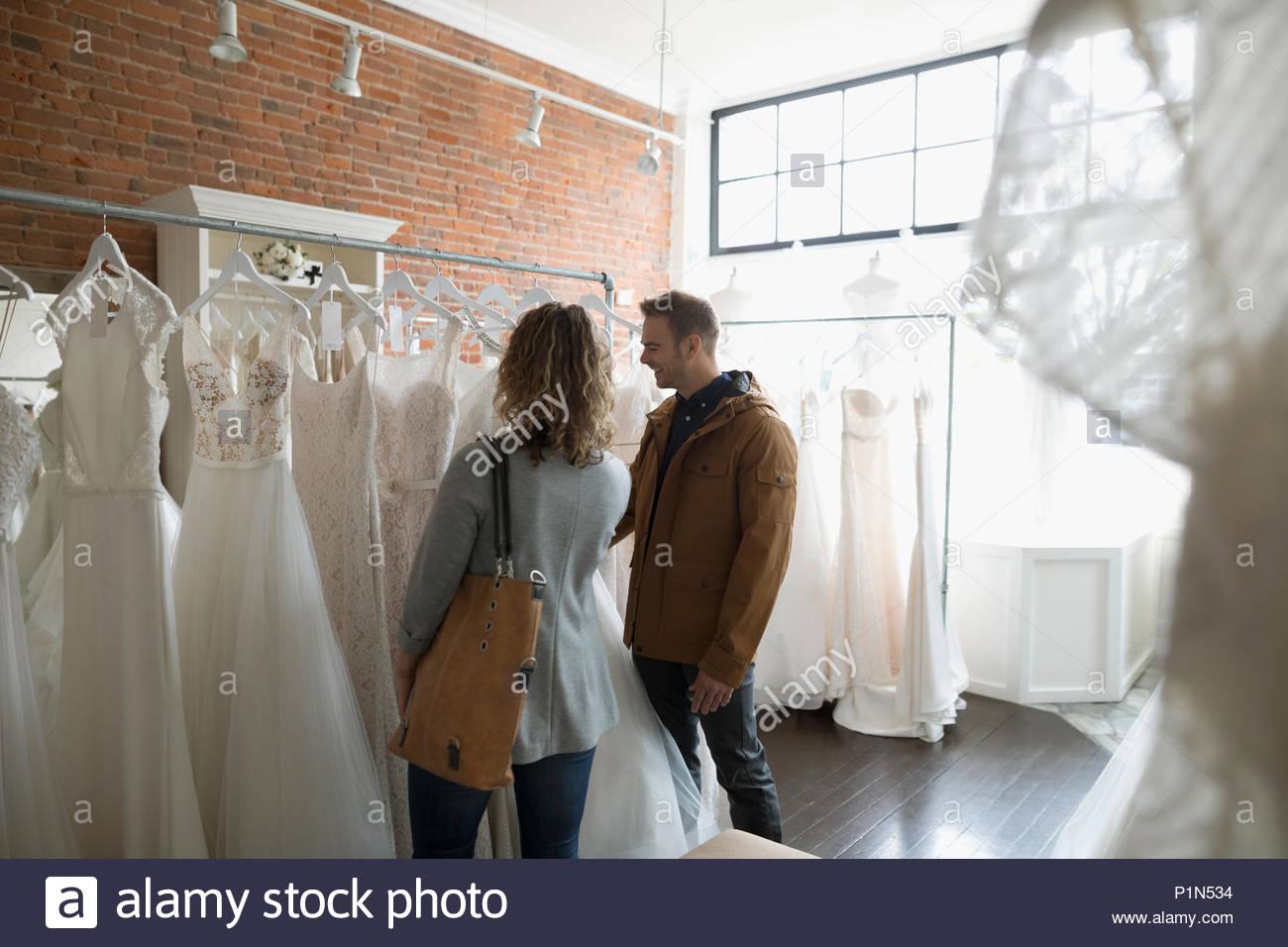 Sposa e lo sposo per lo shopping di abiti da sposa nella boutique nuziale Immagini Stock