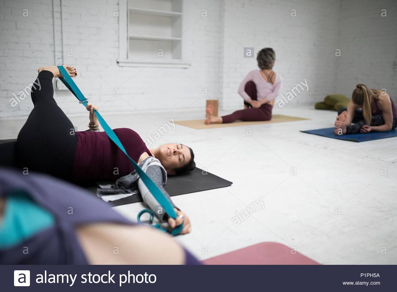 Donna pratica lo yoga delle gambe tratto di crossover con cinturino in classe di yoga Foto Stock