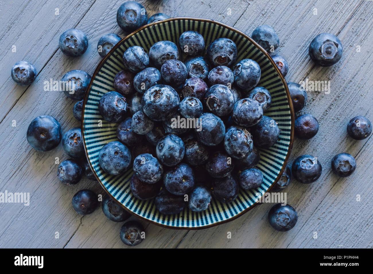 Centrato ciotola di mirtilli con acini sparsi sul tavolo blu Immagini Stock
