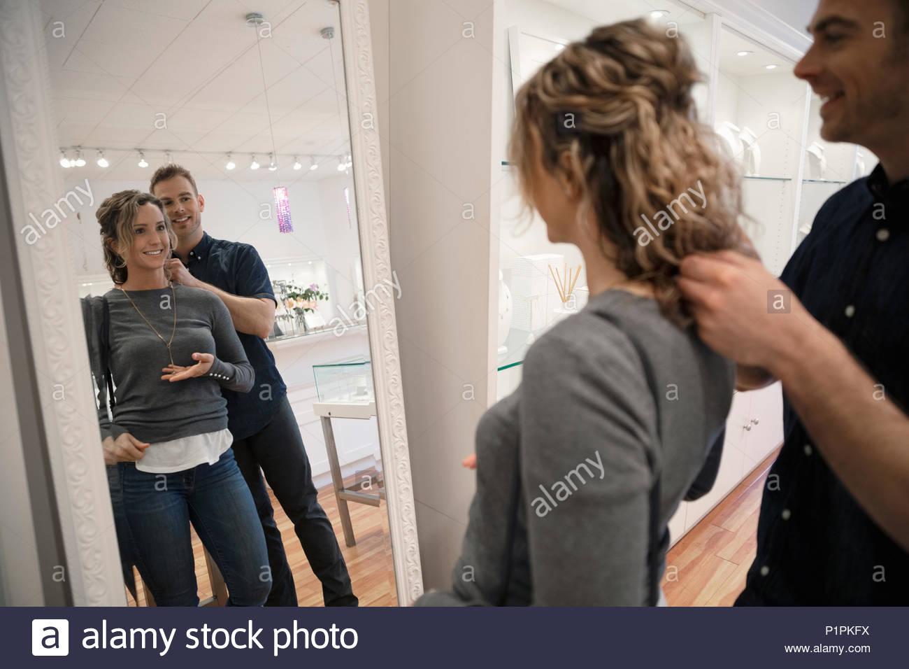 Fidanzato aiutando ragazza provare su collana in gioielleria boutique specchio Immagini Stock