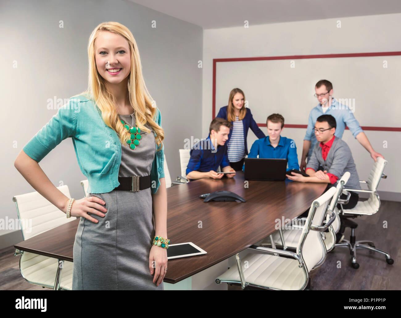 Una giovane e bella la millenaria business donna lavorando sul suo tablet in una sala conferenze con la sua co-lavoratori; Sherwood Park, Alberta, Canada Foto Stock