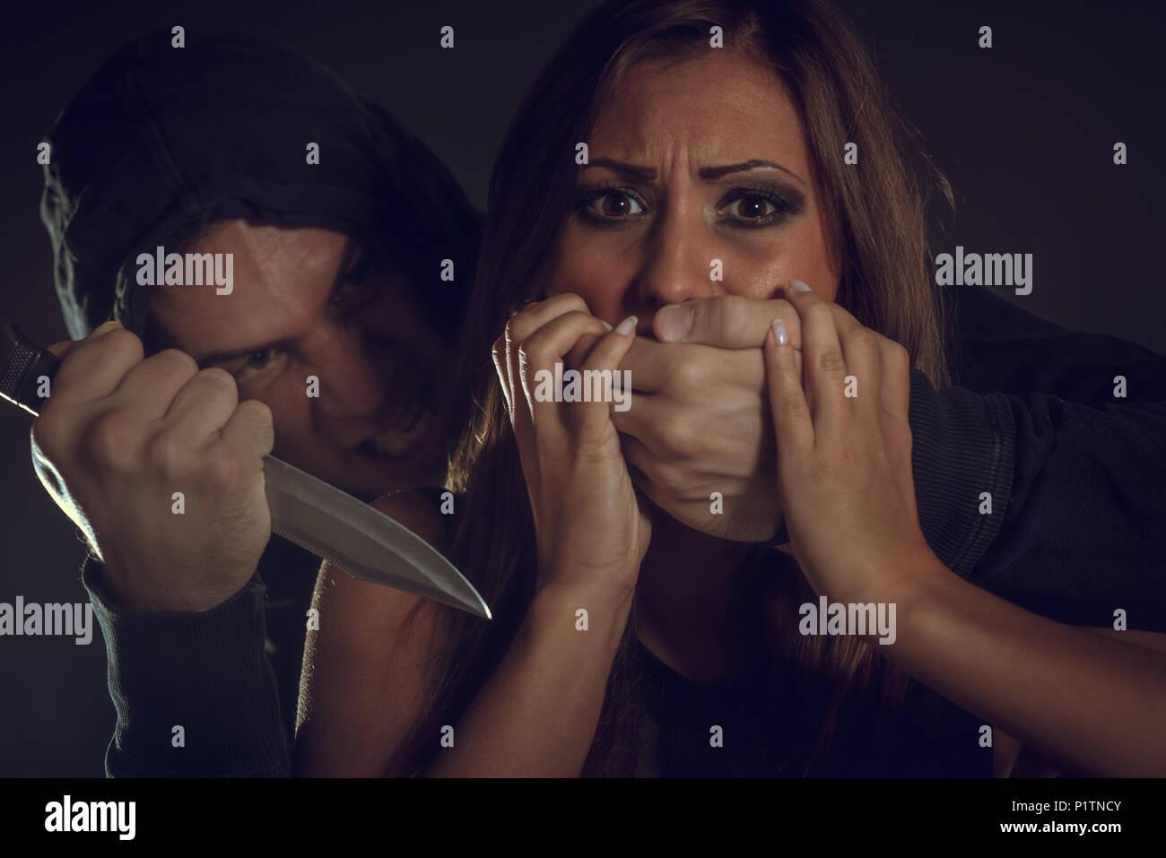 Giovane donna è abusato della vittima di violenza uomo che minaccia con un coltello e mette le mani sulla sua bocca non urlare. Immagini Stock