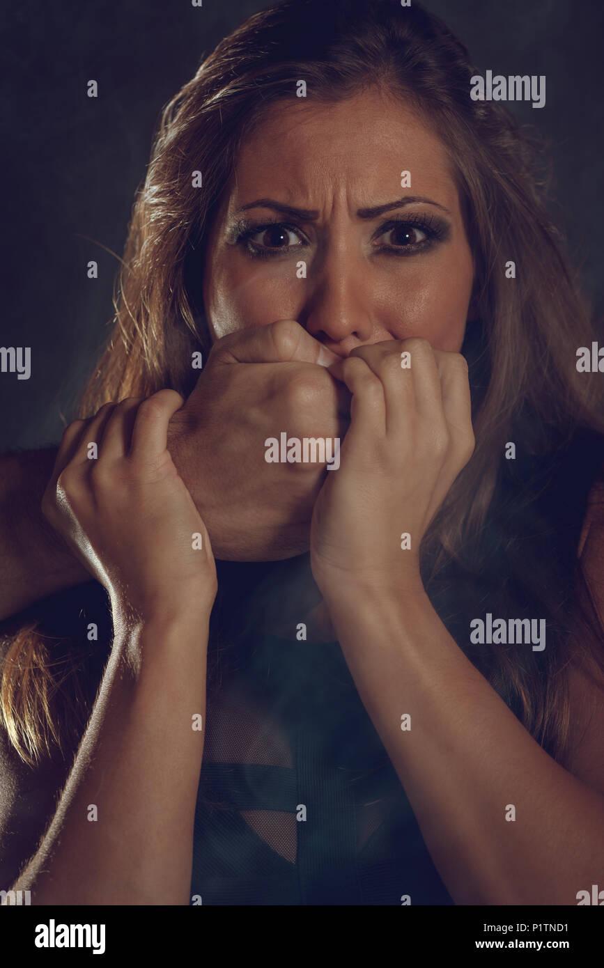 Giovane donna è abusato della vittima di violenza uomo e mette le mani sulla sua bocca non urlare. Immagini Stock