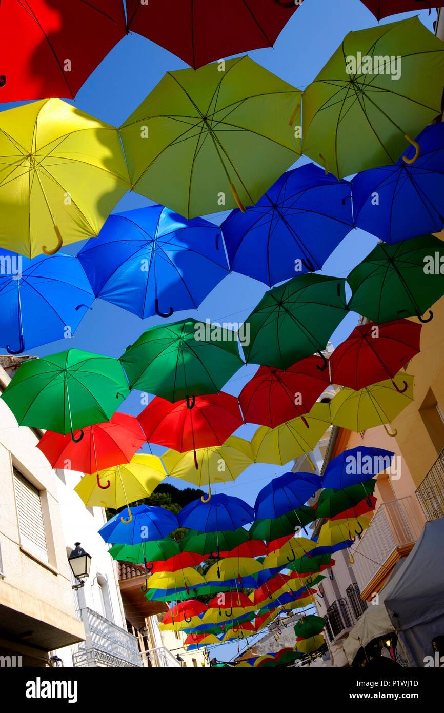 Ombrelloni colorati su strade nel villaggio Spagnolo durante la Fiesta Immagini Stock