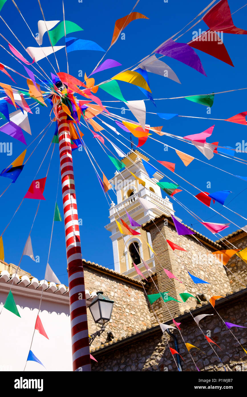 Soleggiato bunting e un colorato pole contro la torre di una chiesa in un piccolo villaggio Spagnolo durante la fiesta. Immagini Stock
