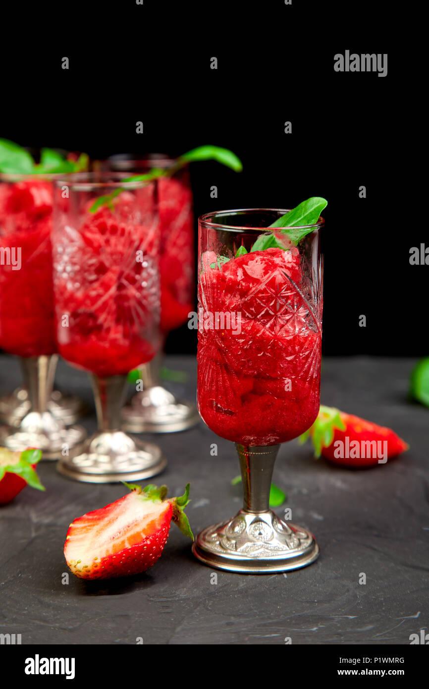 Estate rinfrescante sorbetto di fragole, granite granita di bevande in bicchieri di servizio. Una sana a basso contenuto calorico estate trattare, dessert. Cocktail ghiacciato sul nero backgro Immagini Stock