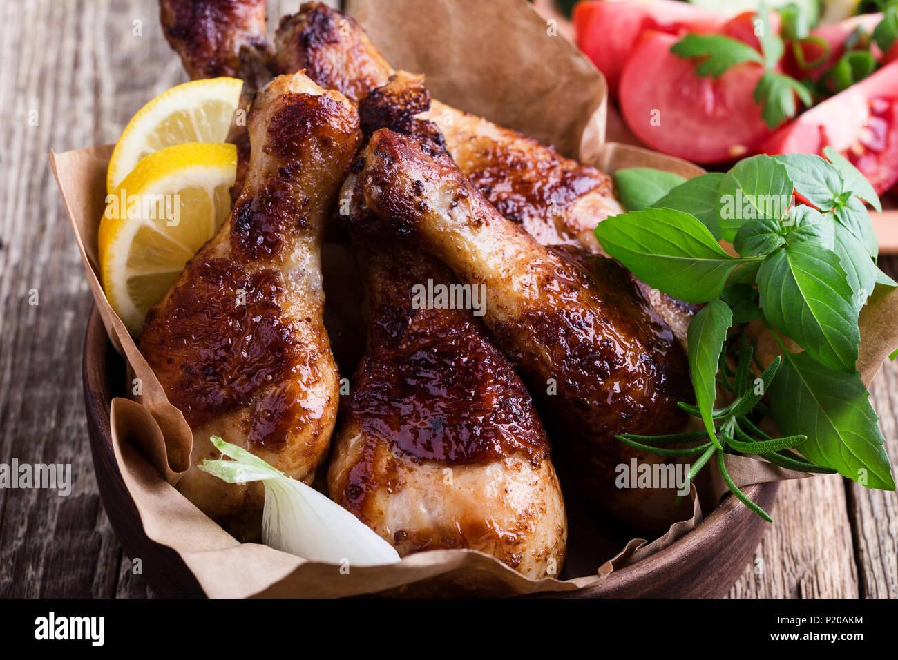 Pollo arrosto cosce di pollo disossate in vaso di ceramica e verdure fresche sulla tavola in legno rustico, cibo preferito Immagini Stock