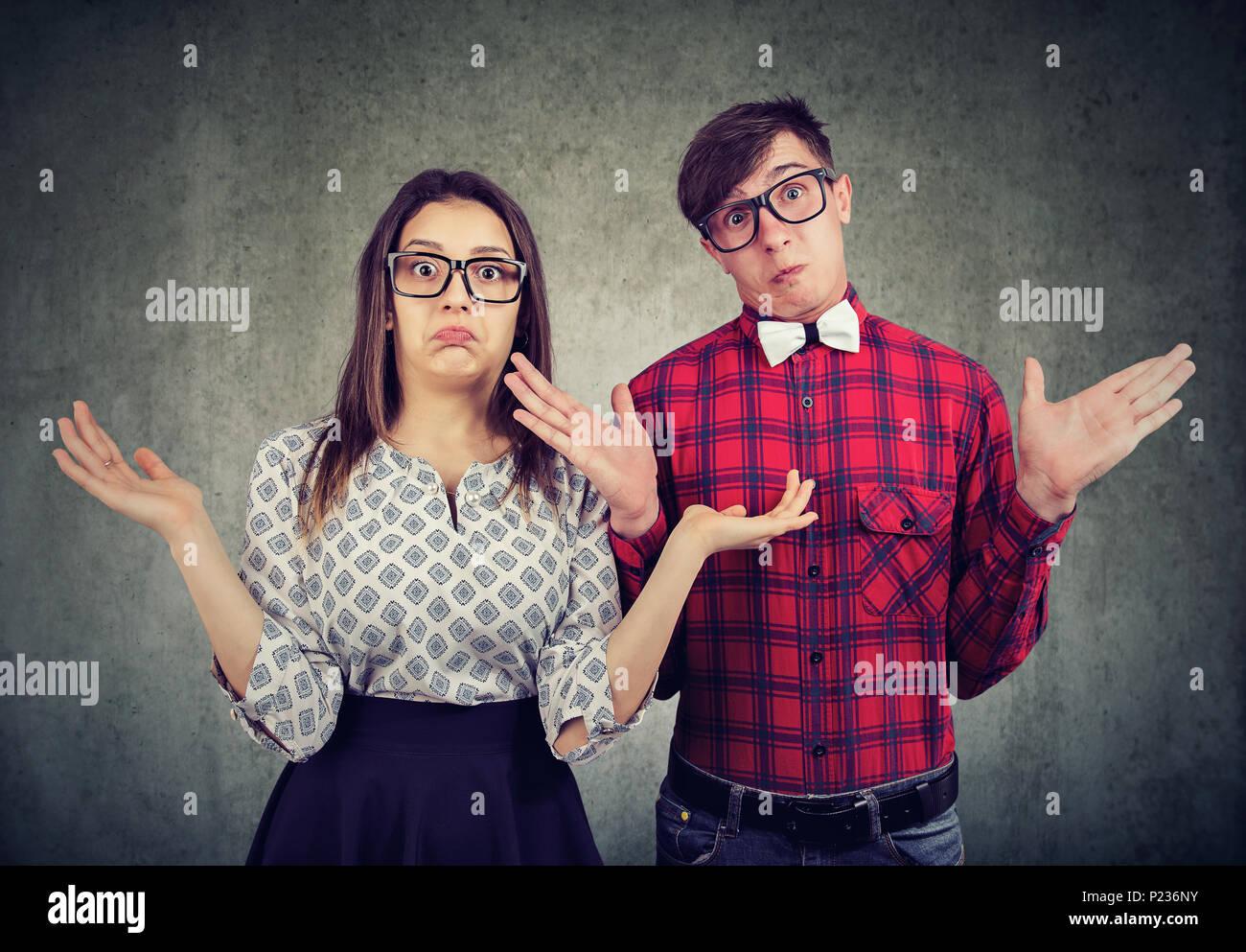 Giovane coppia elegante in bicchieri cercando clueless e alzata di spalle guardando la fotocamera. Immagini Stock