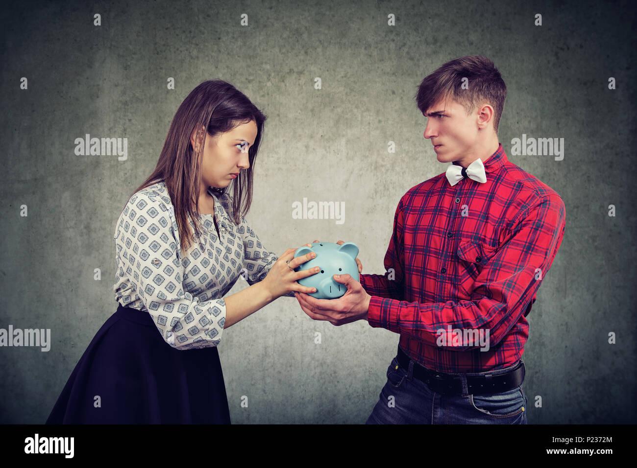 Finanze nel concetto di divorzio. Arrabbiato moglie e marito non può rendere insediamento azienda salvadanaio guardando ogni altro con odio Immagini Stock