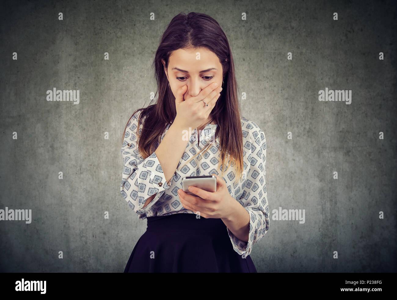 Giovane donna che copre la bocca in stupore durante la lettura del messaggio sullo smartphone cerca storditi. Immagini Stock