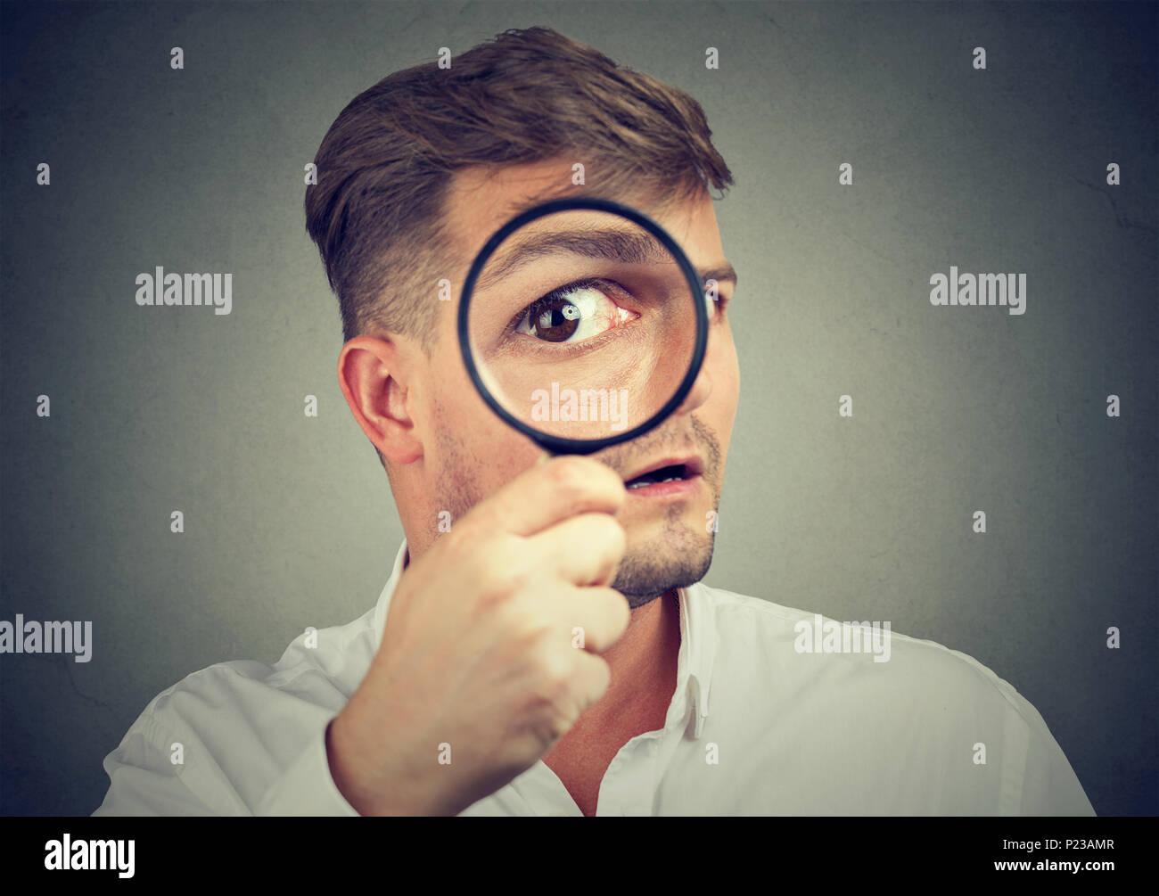 Giovane uomo espressiva cercando scioccati mentre guardando la telecamera attraverso la lente di ingrandimento. Immagini Stock