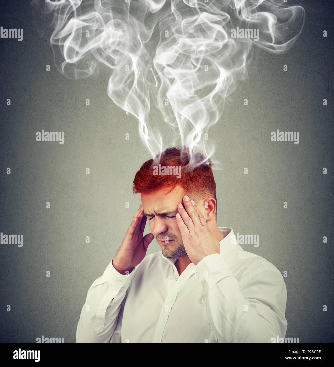 Inquadratura concettuale dell'uomo tenendo le mani sulle tempie e cercando frustrati con fumo che esce fuori di testa. Foto Stock