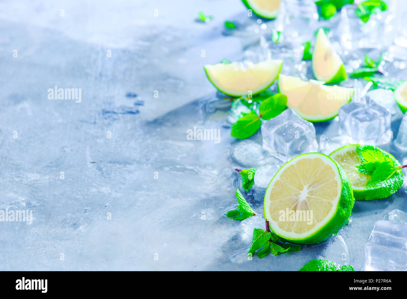 Mint, calce e i cubetti di ghiaccio, cocktail mojito ingredienti testata con copia spazio. Fare bibite estive di close-up. La luce del sole e il concetto di ristoro. Immagini Stock