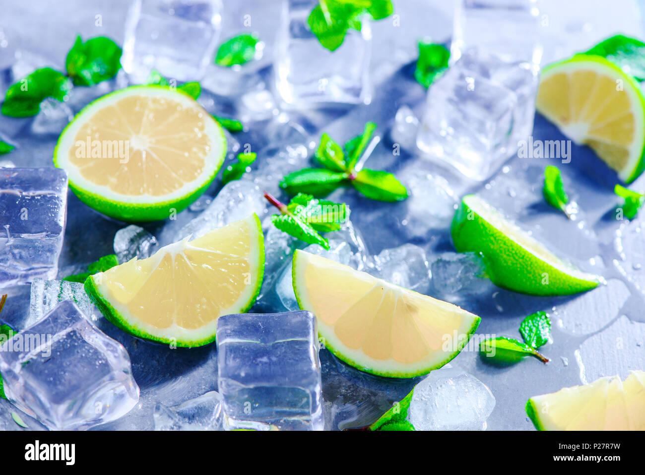 Mint, calce e i cubetti di ghiaccio, cocktail mojito ingredienti testata con copia spazio. Fare bibite estive di close-up. La luce del sole e il concetto di ristoro. Foto Stock