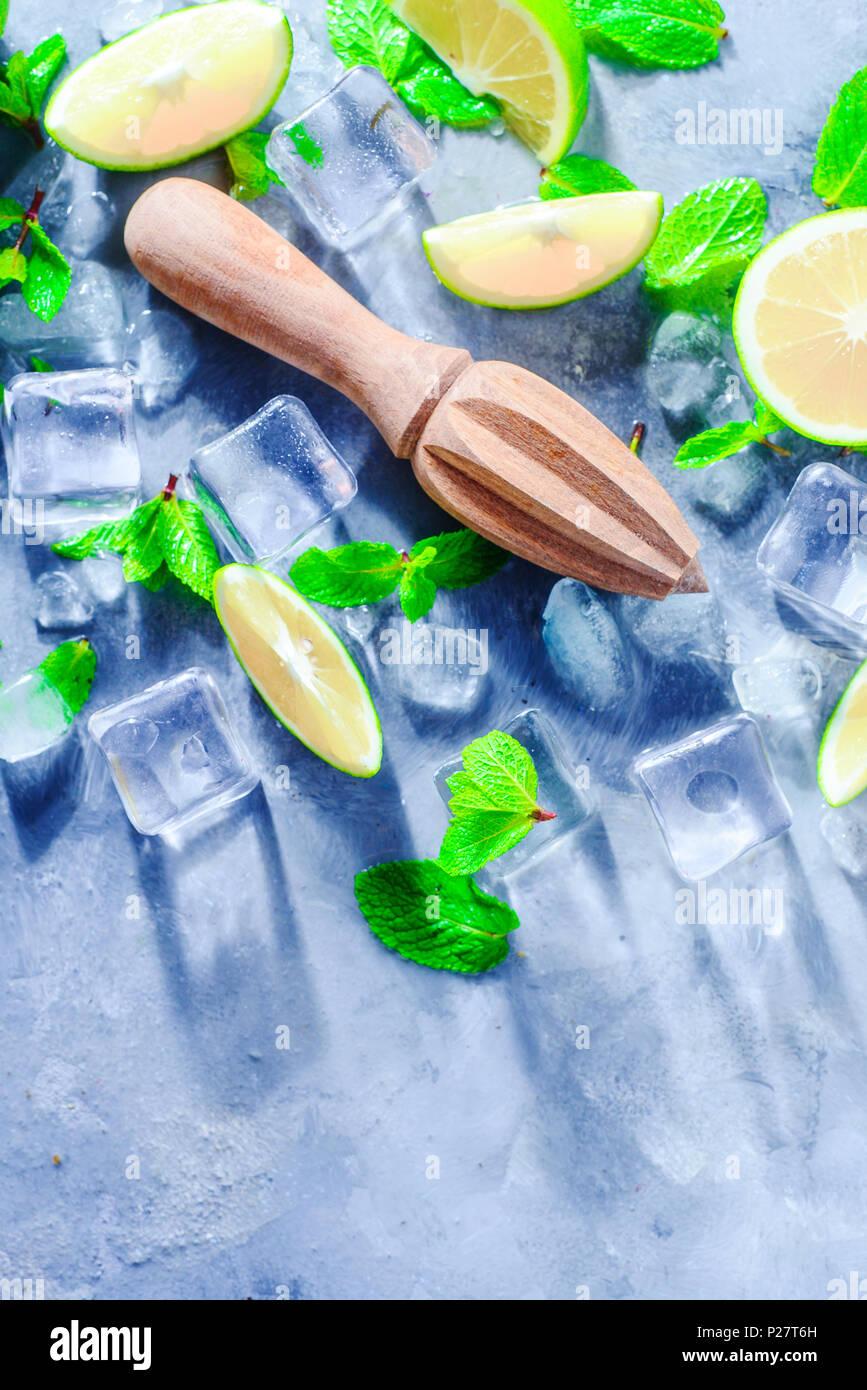 Alesatore di limone o centrifuga con la menta, calce e i cubetti di ghiaccio. Cocktail Mojito ingredienti su una pietra grigio Sfondo con copia spazio. Bevanda estiva concetto sun Immagini Stock