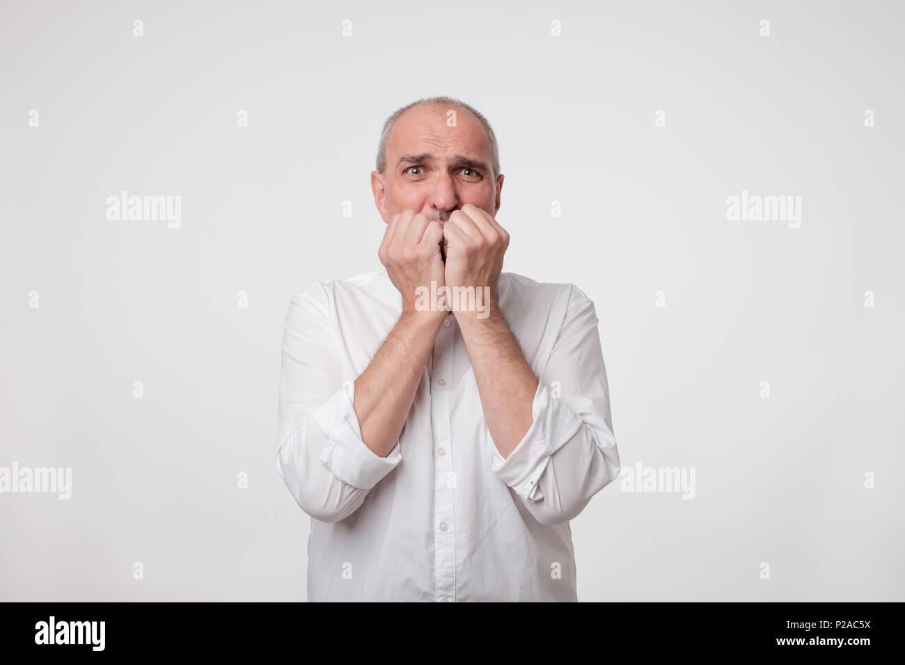Imbarazzato nervoso uomo morde le unghie. Imprenditore maturo sembra preoccupato prima di visitare il medico o il dentista. Ansioso di manager interessati hanno paura di difficile Immagini Stock