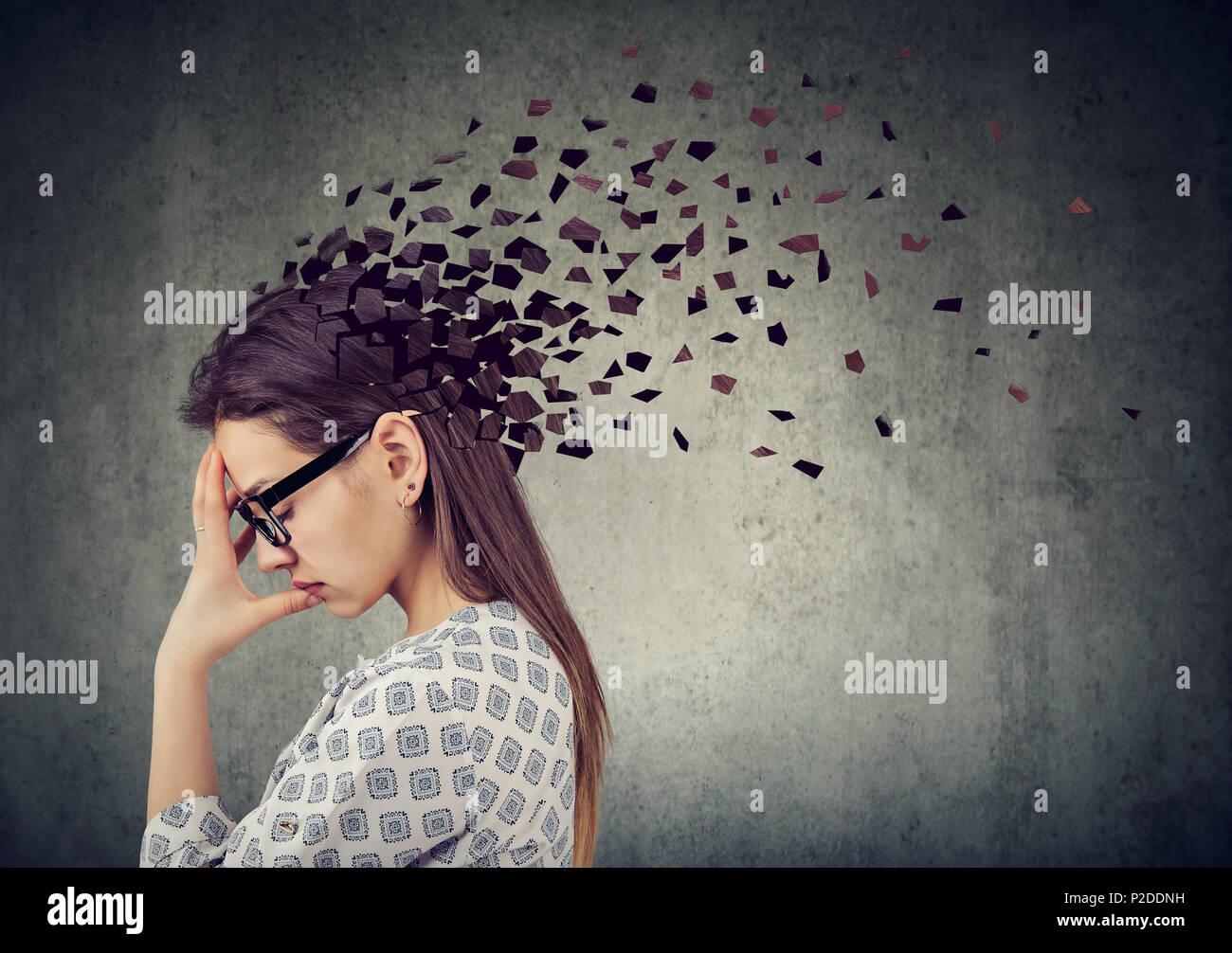 La perdita di memoria a causa di demenza o danni cerebrali. Giovane donna di perdere parti di testa come simbolo della diminuita funzione della mente. Immagini Stock