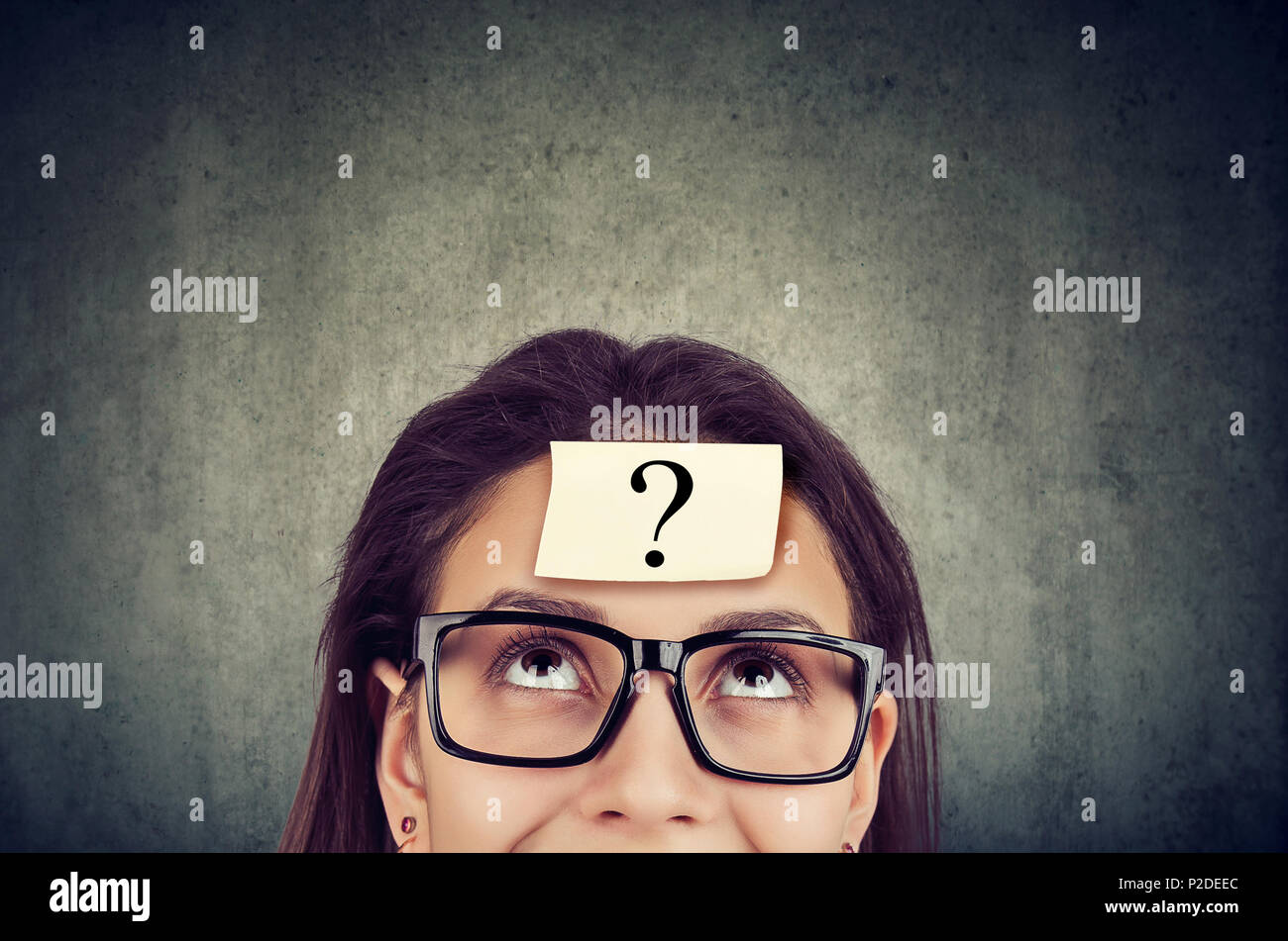 Giovane donna che indossa gli occhiali neri con un punto interrogativo sul fronte guardando verso l'alto. Immagini Stock