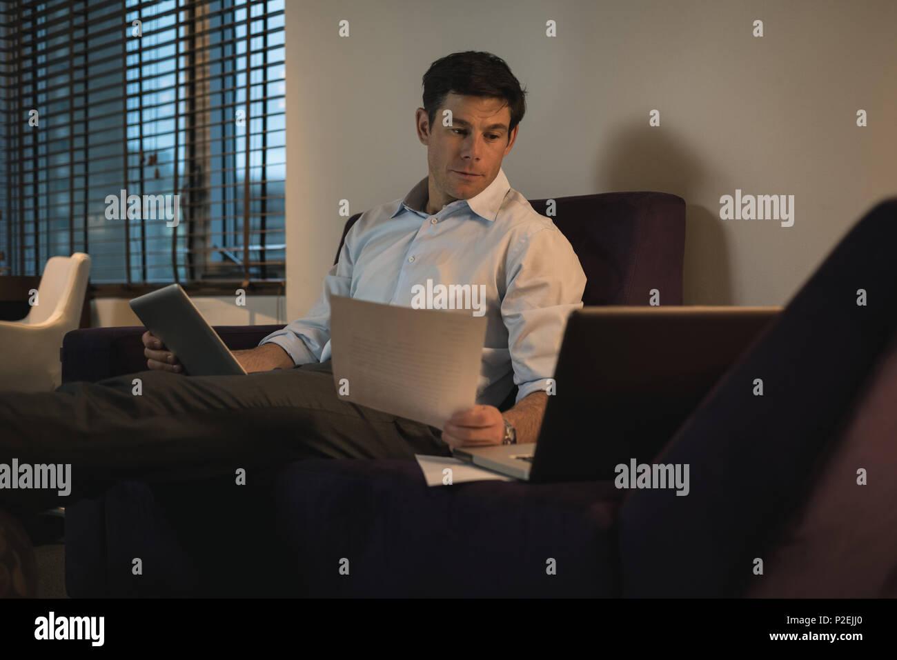 Business man la verifica dei documenti mentre si usa tavoletta digitale Immagini Stock