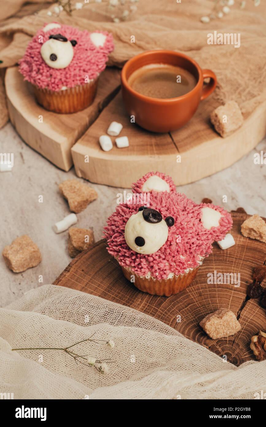 Vista ravvicinata di deliziosi dolci tortine in forma di orsi e la tazza di caffè sul tavolo Immagini Stock