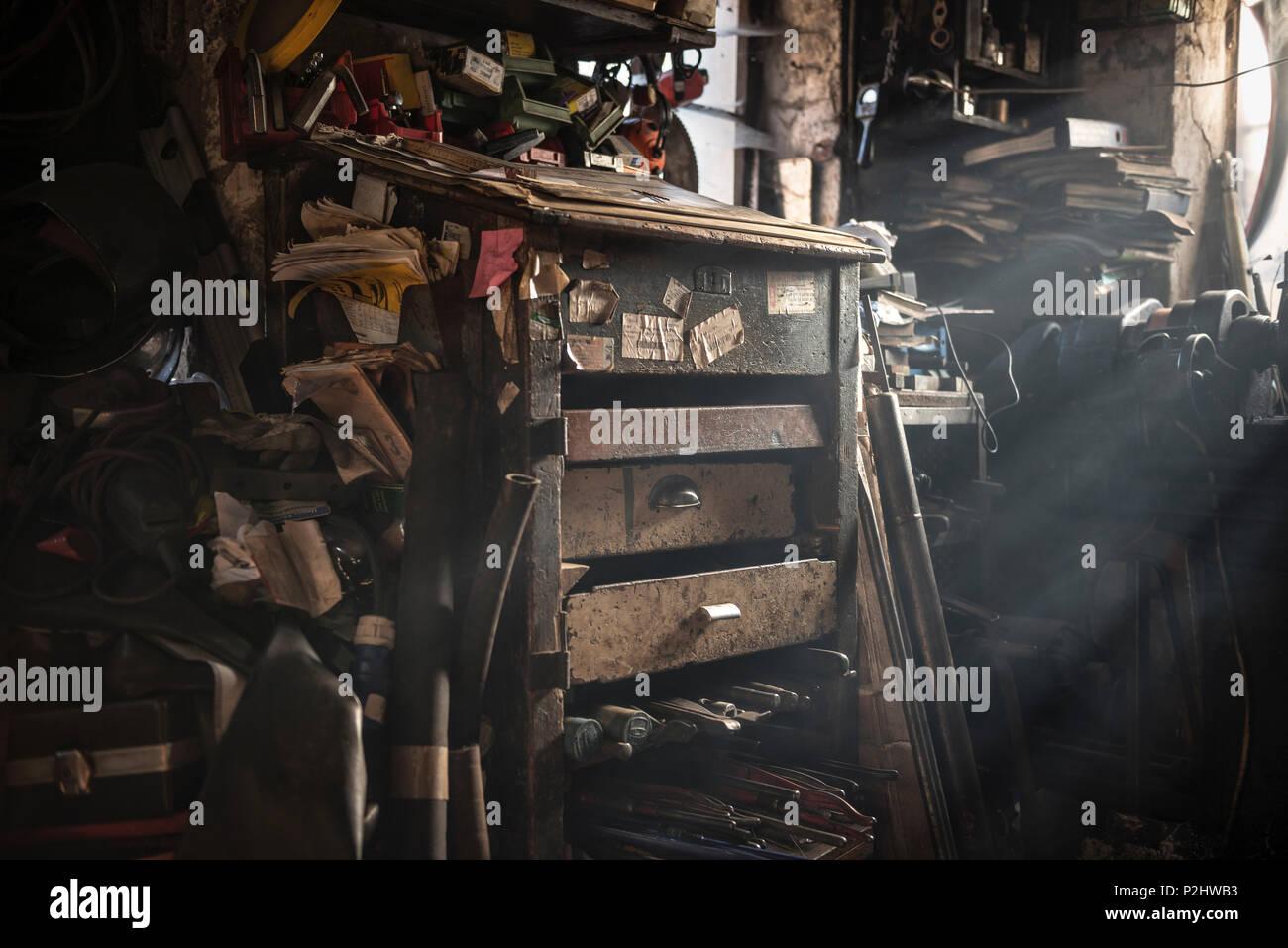 Calda luce che splende attraverso la finestra di un caotico fabbri workshop, Vellberg, Schwaebisch Hall, Baden-Wuerttemberg, Germania Immagini Stock