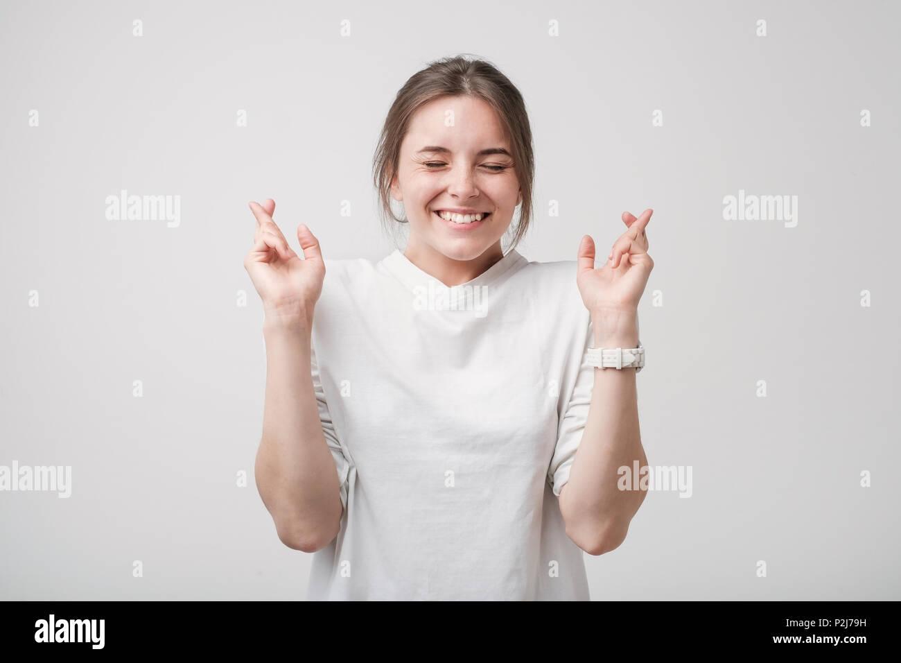 Piscina colpo di attraente ragazza europea in una camicia bianca con sguardo eccitato, mantenendo le dita incrociate a occhi chiusi. Lei ha bisogno di una buona fortuna prima di andare a Immagini Stock
