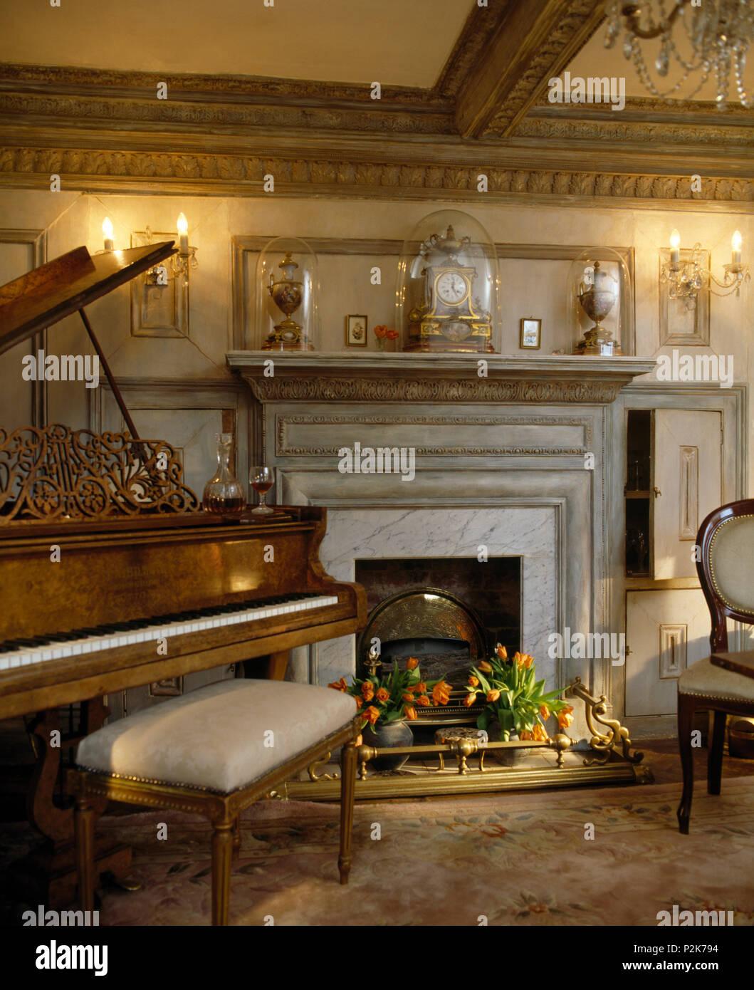 Sgabello Imbottito Al Pianoforte In Opulenta Sala Da Pranzo Illuminata Con Luci A Parete Su Entrambi I Lati Del Camino Foto Stock Alamy