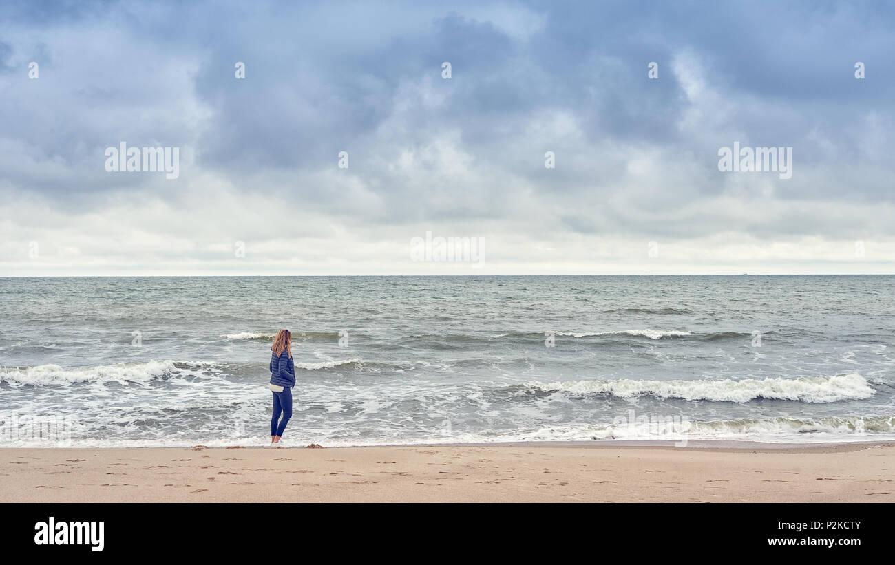 Donna che cammina lungo il bordo del surf su una spiaggia in un blu denim outfit guardando il mare in un freddo giorno nuvoloso con spazio di copia Immagini Stock