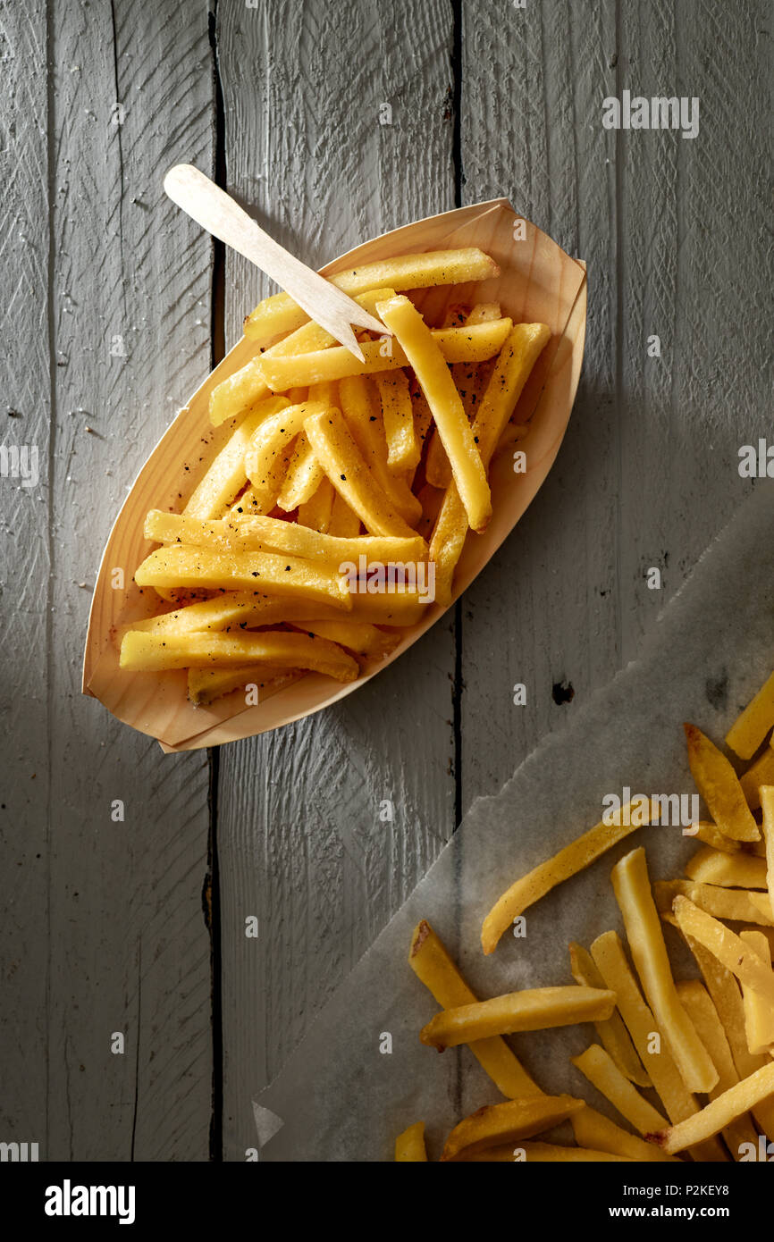 Patate fritte su carta ciotola con forcella in legno Immagini Stock