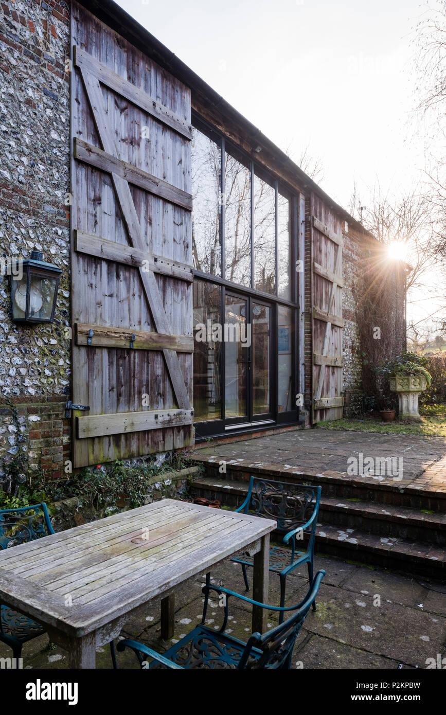 Mobili da esterno sulla terrazza di un fienile conversione con grandi finestre e persiane di legno, Sussex Immagini Stock