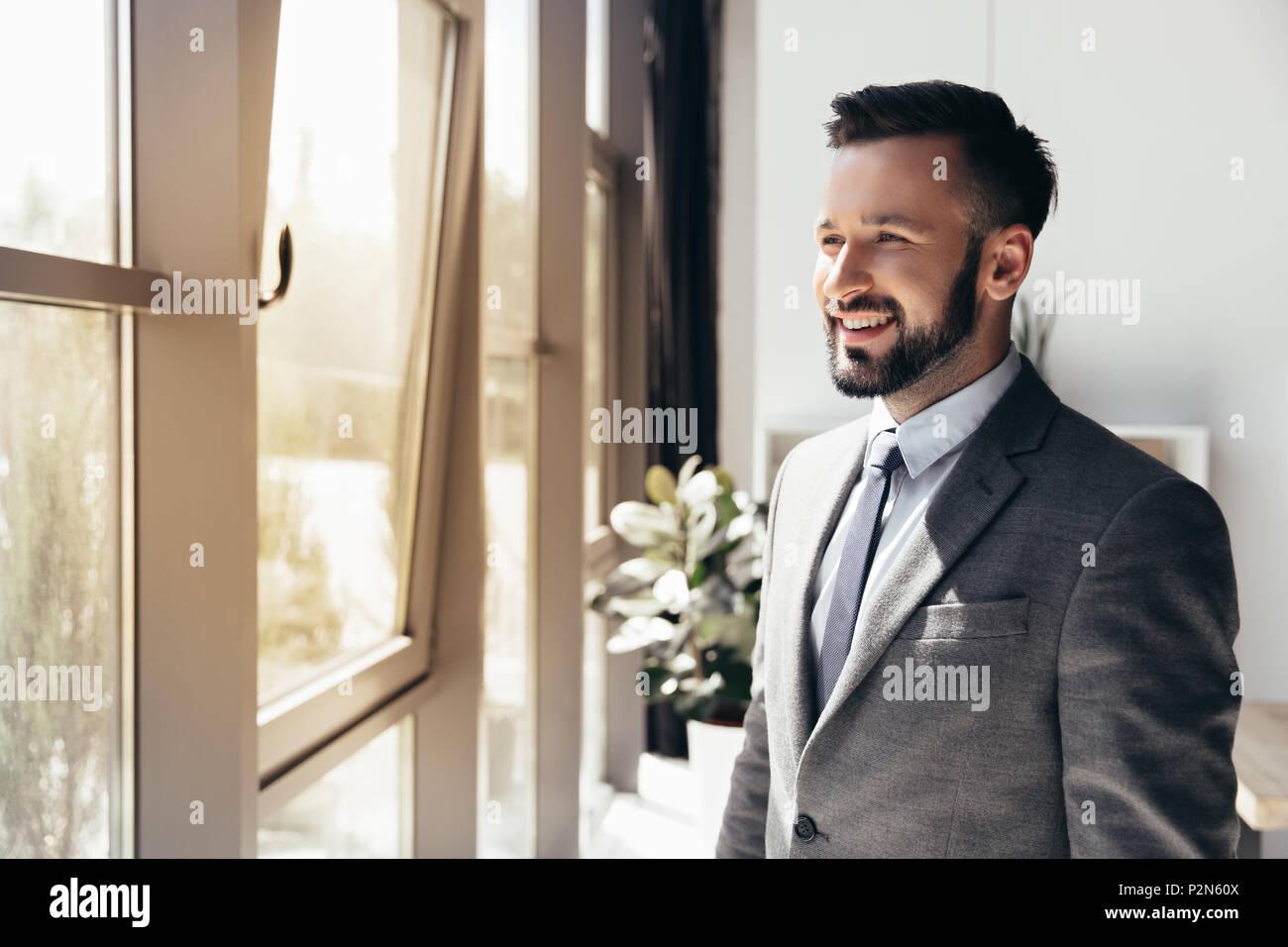Ritratto di imprenditore sorridente in abbigliamento formale che guarda lontano in un ufficio moderno Immagini Stock