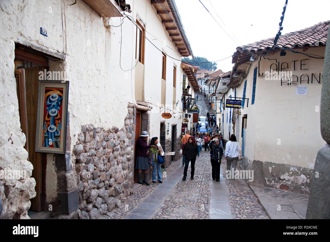 Una tipica strada stretta con la sua pavimentazione in ciottoli in Cusco, Perù Sud America. A sinistra mostra l'ingresso alla Galleria d'arte. Foto Stock