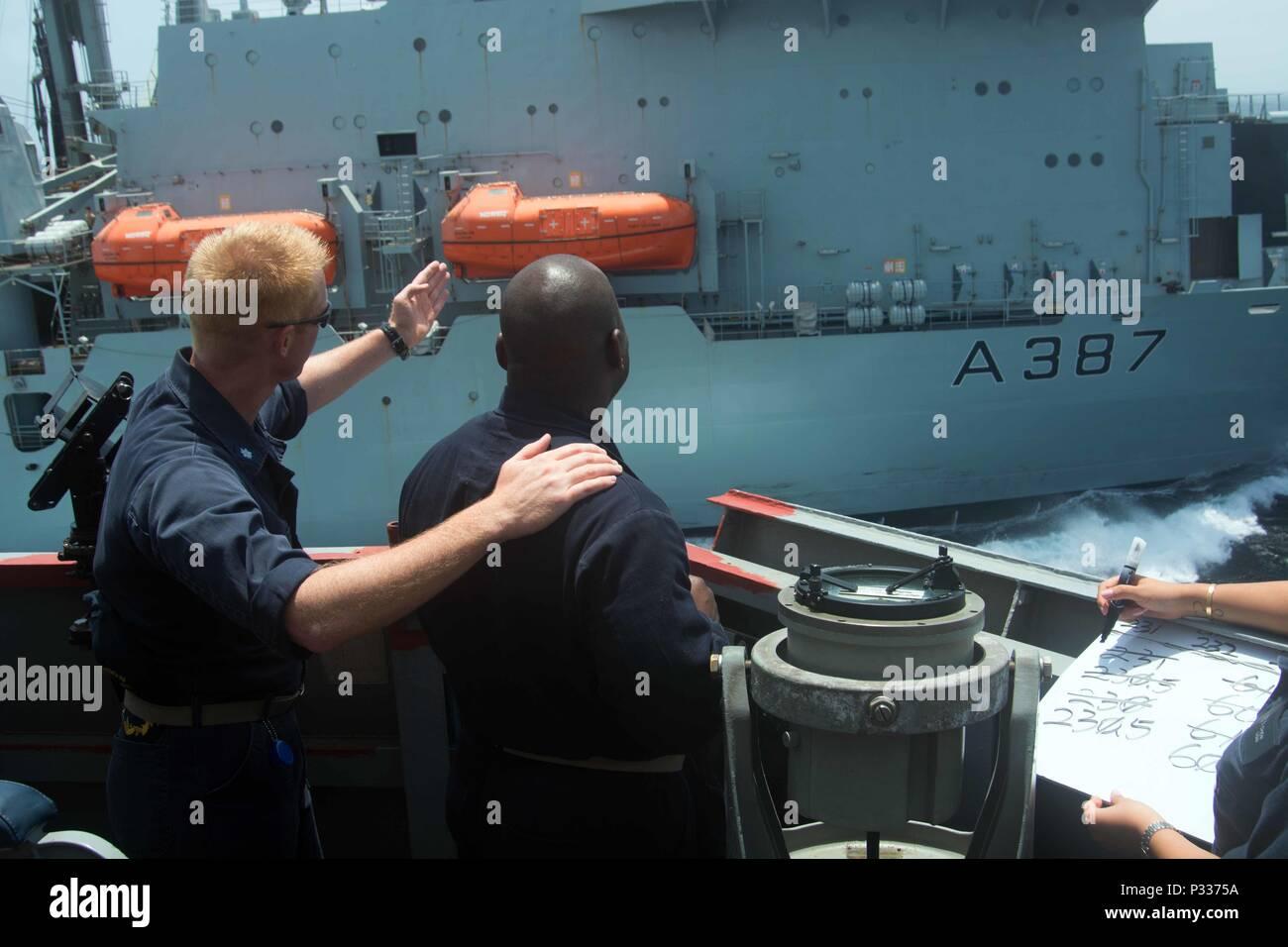 160825-N-CL027-265 Golfo di Oman (Agosto 25, 2016) Lt. Larry Persona, da Riverdale, Ga., agisce come a fianco di conning officer sotto le istruzioni della Cmdr. Stephen W. Aldridge, da Springfield, Virginia, sul ponte di porta ala del guidato-missile destroyer USS Mason (DDG 87) durante un rifornimento in mare con il lubrificatore ausiliario nave rifornimento RFA Fort Victoria . Mason, distribuito come parte di Eisenhower Carrier Strike gruppo, è di sostenere le operazioni di sicurezza marittima e di teatro la cooperazione in materia di sicurezza gli sforzi negli Stati Uniti Quinta Flotta area di operazioni. (U.S. Navy foto di comunicazione di massa Immagini Stock