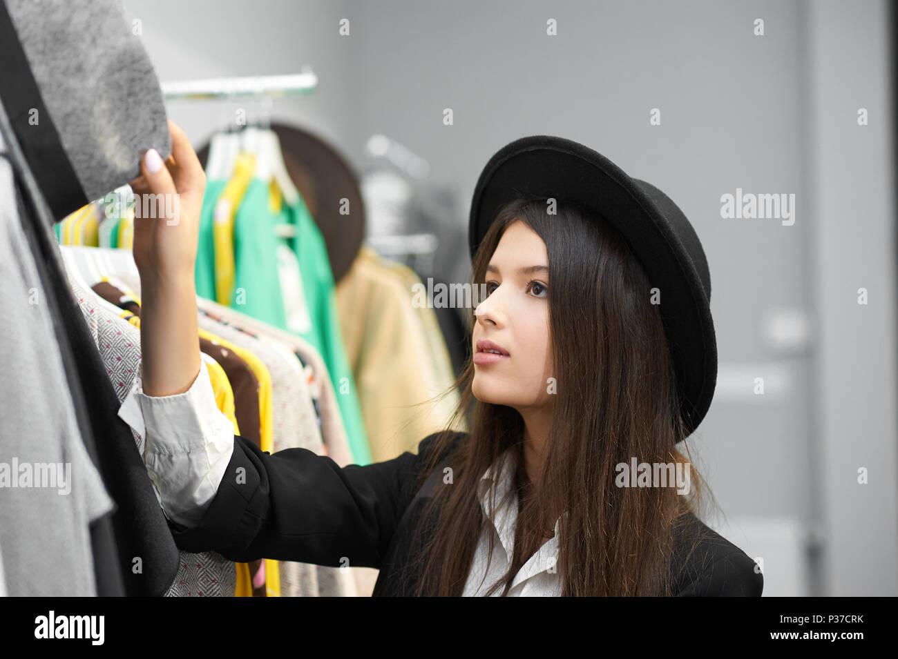 afcca2f4e9b2 Bella ragazza cerca su eleganti e moderni black hats in negozio di  abbigliamento. In piedi