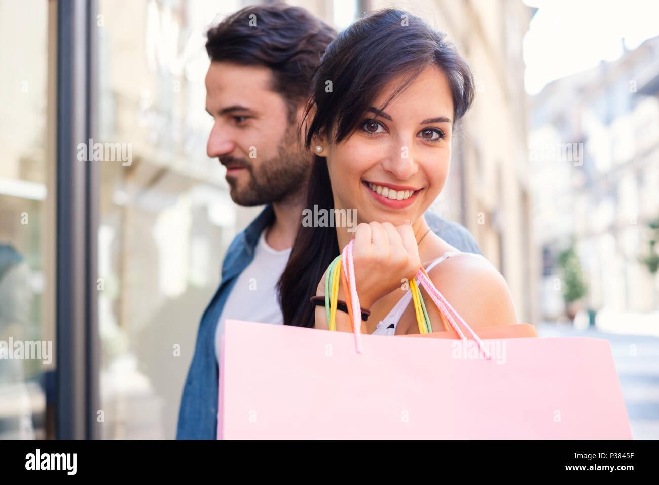 Giovane coppia felice con borse per lo shopping in città durante le vendite stagionali Immagini Stock