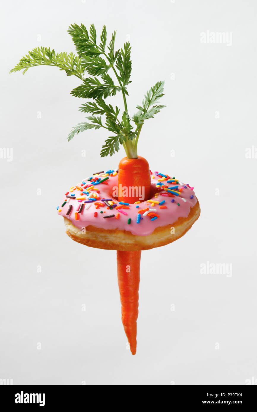 La carota con dolci ciambella rosa Immagini Stock