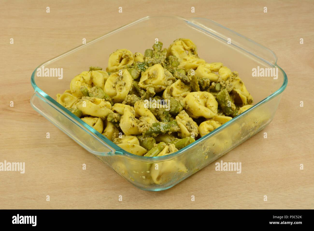 Preparazione dei tortellini di formaggio e pesto di asparagi in casseruola di vetro piatto di cottura in anticipo per una rapida cena nei giorni feriali Immagini Stock