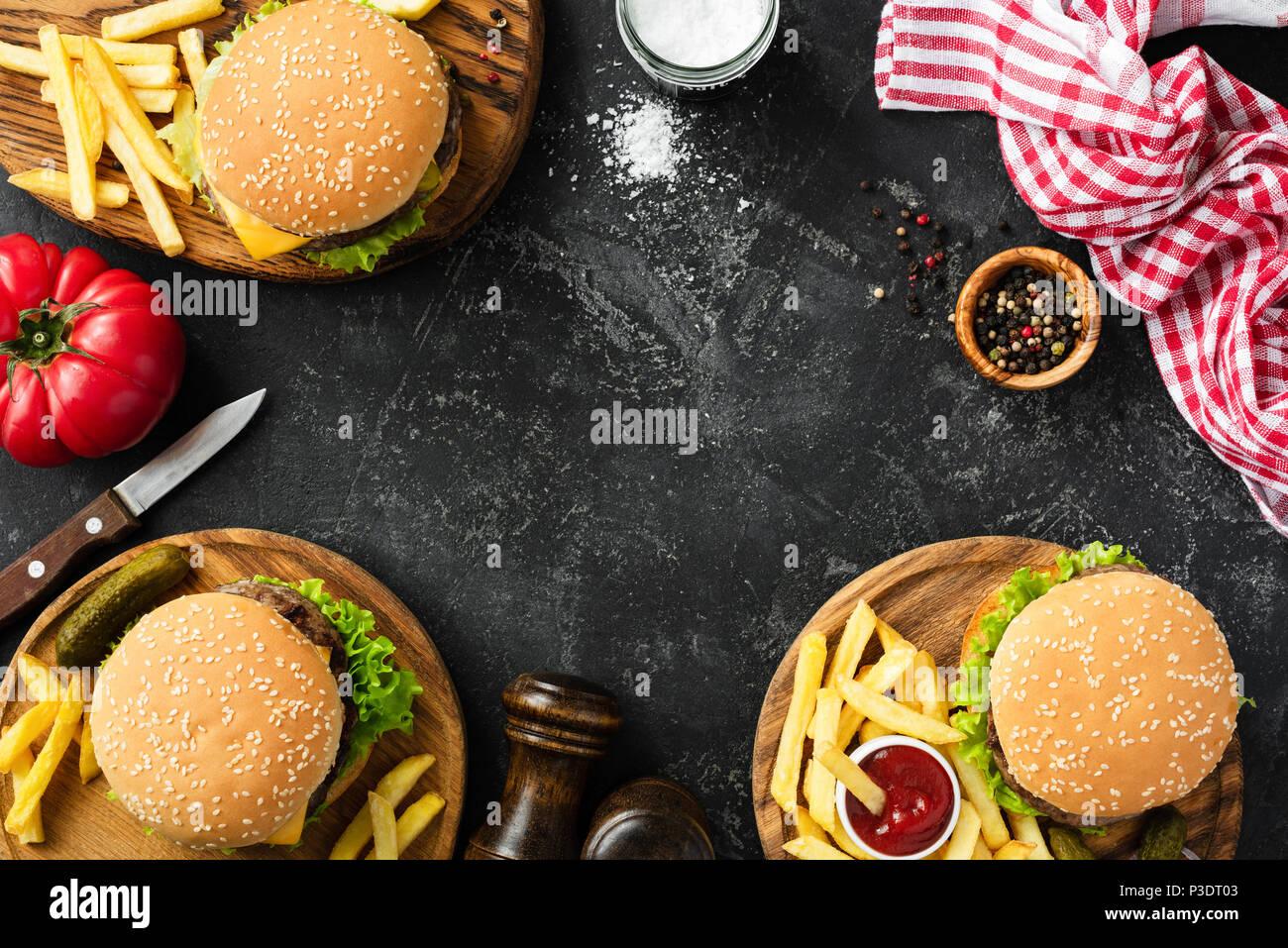 Gli hamburger e patatine fritte in pietra scura sullo sfondo, vista dall'alto con copia spazio. In casa hamburger e patatine fritte. Fast food o concetto BBQ Immagini Stock